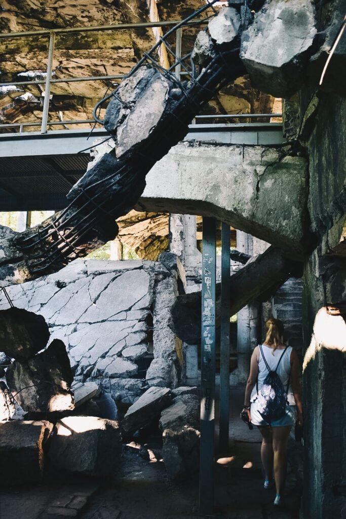 Riuny koszar na Westerplatte od środka i zwiedzająca je turystka.