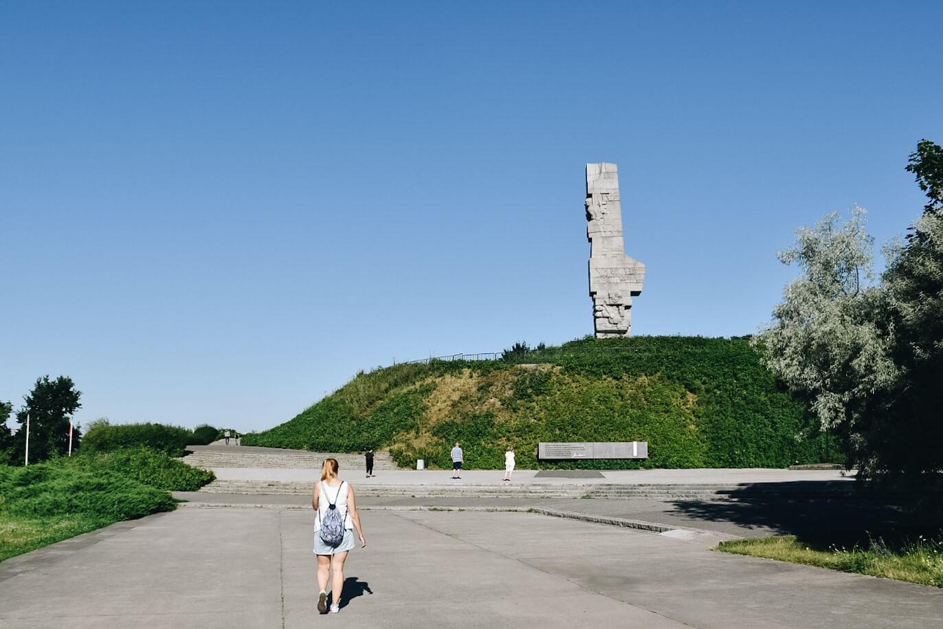 Turystka spacerująca po Westerplatte w tle Pomnik Obrońców Wybrzeża.