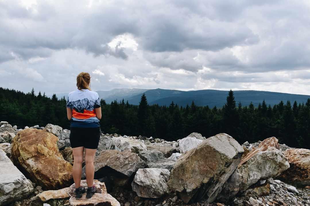 Turystka na kamieniach patrząca na Karkonosze.
