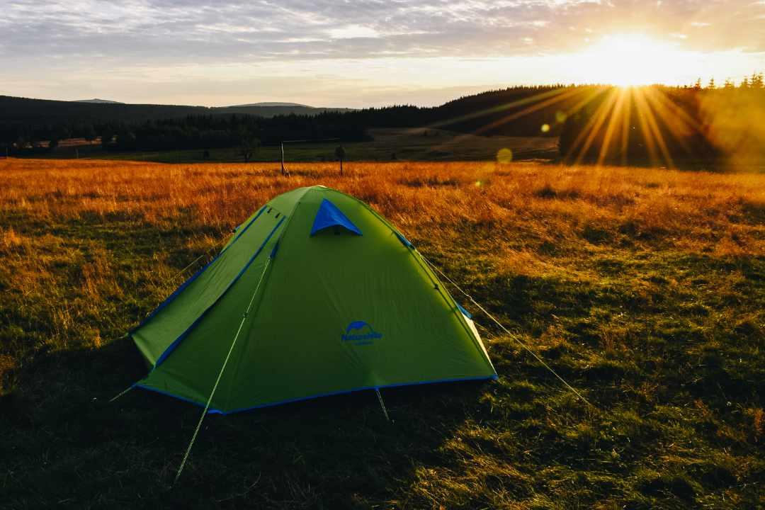 Namiot na górskiej polanie o zachodzie słońca.