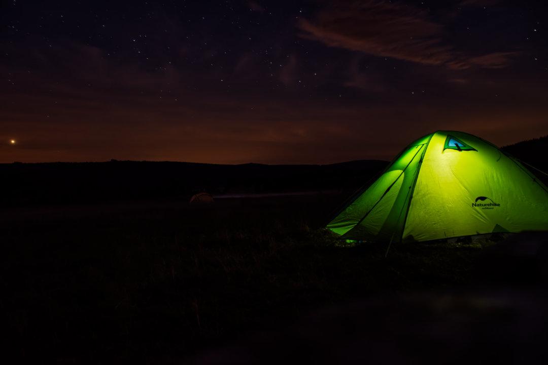 Oświetlony namiot w nocy przy rozgwieżdżonym niebie.