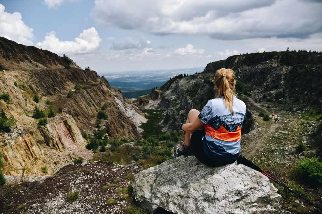 Opuszczona kopalnia kwarcu w Górach Izerskich. Turyska siedząca na kamieniu.
