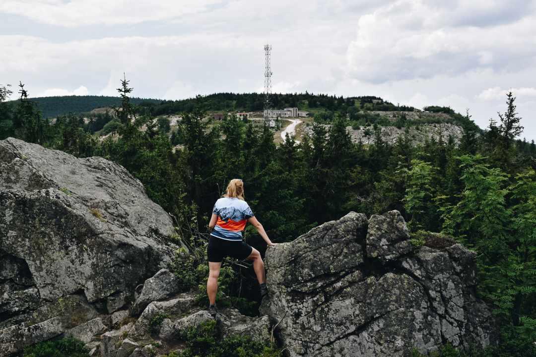 Turystka na skałach patrząca na opuszczoną kopalnia kwarcu w Górach Izerskich.