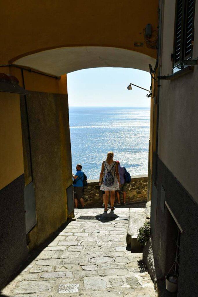 Turystka wychodząca na taras widokowy na morze w miasteczku Corniglia.