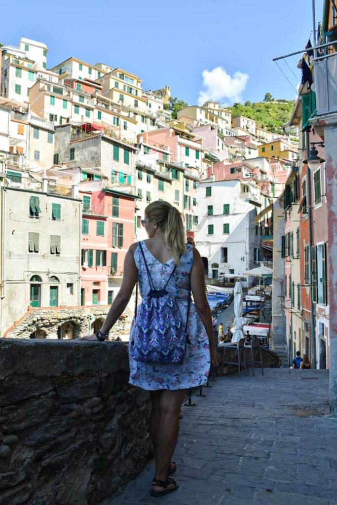 Turystka na ulicach Cinque Terrre. Widok na kolorowe kamienice.