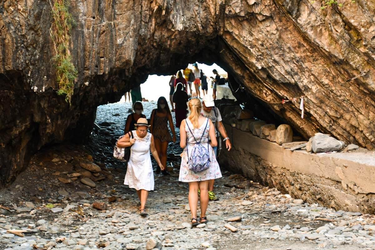 Turyści przechodzący na plaże skalnym tunelem.